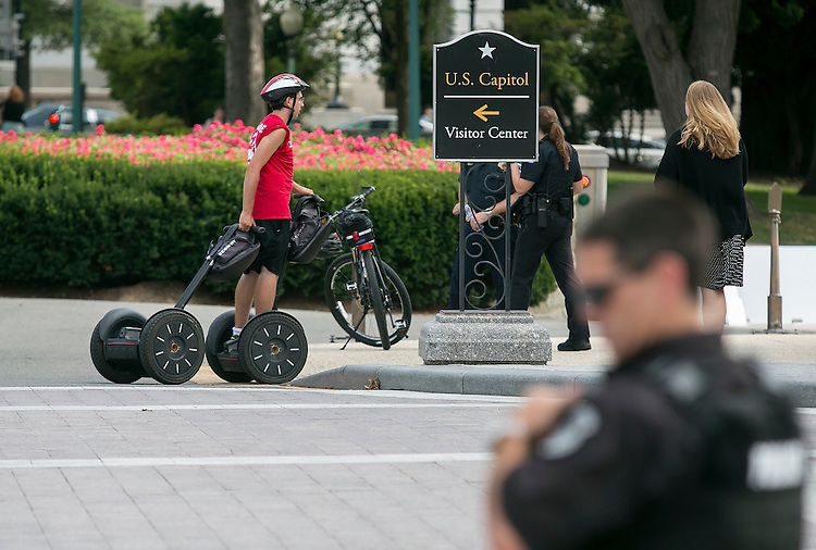 UNITED STATES - JULY 29: A tour leader carries an extra segway while tourists pass the House steps at the Capitol before the final votes before the August recess on Wednesday, July 29, 2015. The House of Representatives will not meet again until September 8, 2015. (Photo By Al Drago/CQ Roll Call)
