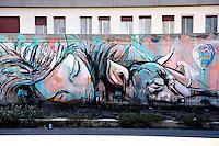Straniera, Artista Alice'<br /> Title Foreigner artist Alice'<br /> La pittura di Alice Pasqualini, in arte Alice', si distingue per il gioco luministico tra colori caldi e freddi. In questo murales l'arancio rappresenta il colore dei palazzi al tramonto, in contrapposizione all'azzurro del cielo. <br /> Roma 01-02-2015 Street Art a Roma. In vari quartieri di Roma e' fiorita la Street Art, con splendidi murales che hanno lo scopo di raccontare delle storie della citta', di commemorare dei momenti importanti, o semplicemente di interpretarla.<br /> Street Art in Rome. Very important writers  painted Murales in various districts of Rome to tell stories about the city, to commemorate important moments, to embellish the quarter or simply to portray it.  <br /> Photo Samantha Zucchi Insidefoto