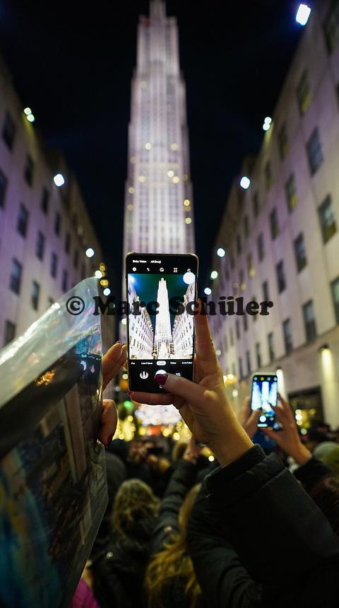 Besucher machen Bilder vom Weihnachtsbaum und dem Rockefeller Center in New York - 08.12.2019: New York