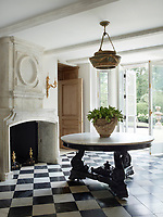 The front hall's Indian table and English chandelier and chair are 19th-century and the 17th-century fire- place is limestone; the black and white check pattern marble flooring is by Exquisite Surfaces. A set of French doors open onto the terrace beyond.