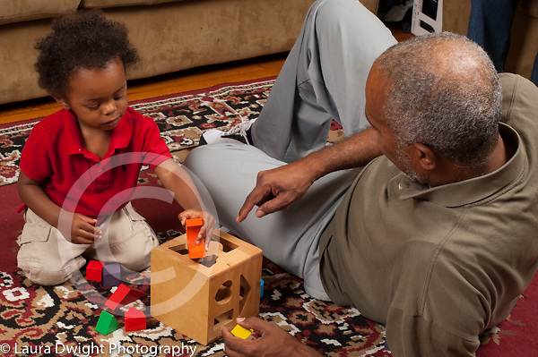 16 month old toddler baby boy playing with shape sorter toy and grandfather horizontal