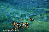 Natal, Brazil. Group of schoolgirls snorkelling in the clear blue green water of the Atlantic Ocean.