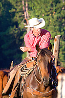 Western cowboy wearing red striped shirt and white cowboy hat, astride a brown chestnut horse, leaning forward with arms crossed, resting or thinking for a moment.