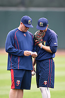 Cedar Rapids Kernels pitching coach J.P. Martinez (left) talks with pitcher Dereck Rodriguez (31) during practice before the first game of a doubleheader against the Kane County Cougars on May 10, 2016 at Perfect Game Field in Cedar Rapids, Iowa.  Kane County defeated Cedar Rapids 2-0.  (Mike Janes/Four Seam Images)