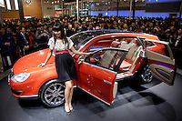 Visitors look at a model posing near a newly designed Volkswagen Neeza unveiled at the 9th Beijing International Automotive Exhibition in Beijing .25 Nov 2006