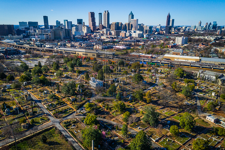 Historic Oakland Cemetery with Atlanta, Georgia, USA skyline and CSX train yard.