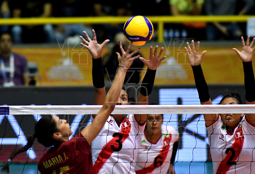 BOGOTÁ-COLOMBIA, 09-01-2020: Brenda Uribe y Diana de la Peña de Perú, intentan un bloqueo al ataque de balón a María José Pérez de Venezuela, durante partido entre Perú y Venezuela, en el Preolímpico Suramericano de Voleibol, clasificatorio a los Juegos Olímpicos Tokio 2020, jugado en el Coliseo del Salitre en la ciudad de Bogotá del 7 al 9 de enero de 2020. / Alexandra Muñoz and Maricarmen Guerrero from Peru, trie to block the attack the ball to Maria Jose Perez from Venezuela, from Venezuela, during a match between Venezuela and Peru, in the South American Volleyball Pre-Olympic Championship, qualifier for the Tokyo 2020 Olympic Games, played in the Colosseum El Salitre in Bogota city, from January 7 to 9, 2020. Photo: VizzorImage / Luis Ramírez / Staff.