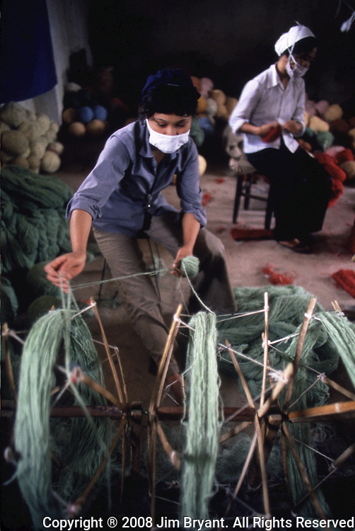 A Hai Hung Rug factory worker weaves strands of wool into balls to be used in the rug making in Hanoi, North Vietnam.  Eighty percent of the workers are women, who manage families and juggle budgets after work. (Jim Bryant Photo).....