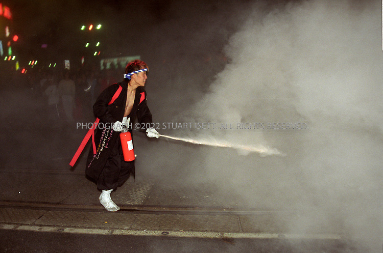 11/18/1999--Hiroshima, Japan..A  bosozoku gang member afires a fire extinguisher off at police during night of rioting on the streets of Hiroshima. Such gangs have been common in Japan for many years and are considered stepping stones to join yakuza gangs and 'uyoku' or rightwing nationalsist groups....All photographs ©2003 Stuart Isett.All rights reserved.This image may not be reproduced without expressed written permission from Stuart Isett.