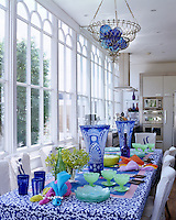 A kitchen/dining room in a conservatory extension in which the table is laid with blue and white and coloured glassware