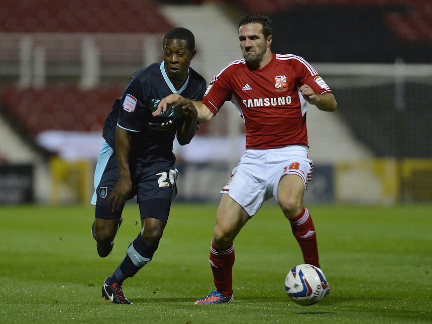 Burnley's Marvin Bartley battles with Swindon Town's Tommy Miller ..Football - Capital One Cup Third Round - Swindon Town v Burnley - Tuesday 25th September 2012 - The County Ground - Swindon. .