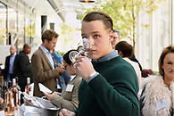 Cupping a glass of wine at a tasting event.