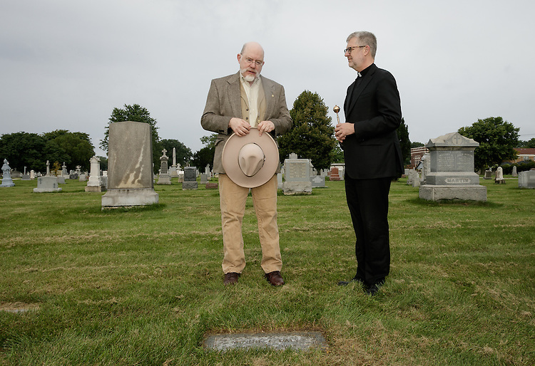 """Bro. Mark Elder, C.M., artist and muralista in the Department of Art, Media and Design, left, with the Rev. Dennis H. Holtschneider, C.M., president of DePaul, says a eulogy over the gravesite of Minnie Daly, Saturday, Sept. 10, 2016, at Calvary Catholic Cemetery in Evanston. In his eulogy Elder said of Daly """"We honor your memory today Minnie. We honor it and bless it.  We do this because of your great care for children in your work.  And because of the great example in education you gave others."""" Holtschneider blessed the grave with holy water following the eulogy. Minnie Daly, the first lay female graduate of DePaul in 1914, was buried in her sister's grave (Florence Daly) without any marker. DePaul recently provided a new grave marker to indicate the site of her burial. (DePaul University/Jeff Carrion)"""