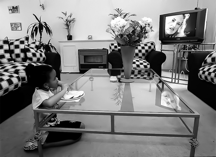 Connie Pietersen, 7, watches television while eating a mango in her family's home in Houghton, Johannesburg.  With her father in the cell phone business, Connie's family is part of the growing black elite in post-apartheid South Africa.  They live in a large house in one of the most expensive neighborhoods in Johannesburg, have multiple servants and both parents drive BMWs.