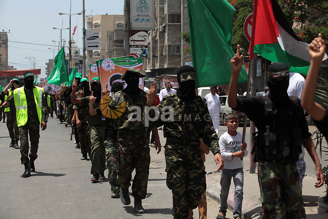 Palestinian Hamas militants take part in a demonstration in solidarity with prisoners held in Israeli jails, and in support of the people in the West Bank, in Nuseirat refugee camp in the center of the Gaza Strip, June 20, 2014. Israel has launched a wide-ranging military operation aimed at finding the Israeli teenagers that believed kidnapped by Hamas and crushing the movement's infrastructure in the West Bank. Photo by Ashraf Amra