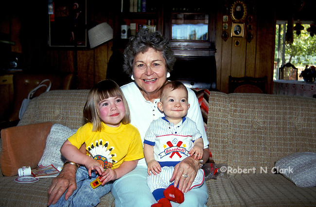 Little girl and little boy with grandmother on sofa, kids smiling