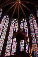 Low angle view (through the reliquary) of the choir of the upper chapel of La Sainte-Chapelle (The Holy Chapel), 1248, Paris, France. The upper chapel has a seven section choir. Each window group has two lancets. Fifteen huge mid-13th century windows fill the nave and apse. La Sainte-Chapelle was commissioned by King Louis IX of France to house his collection of Passion Relics, including the Crown of Thorns, and is considered among the highest achievements of the Rayonnant period of Gothic architecture. Picture by Manuel Cohen