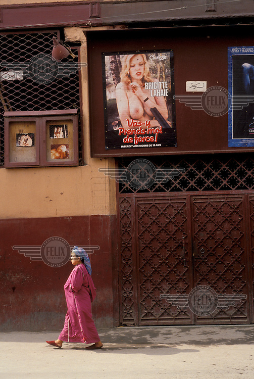 © Jean Leo Dugast / Panos Pictures..Marrakech, Morocco...Woman passing cinema posters for racy French films.