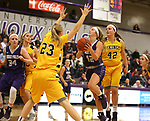 SIOUX FALLS, SD - DECEMBER 31: Kaely Hummel #12 from the University of Sioux Falls drives to the basket against Naomi Rust #42 and Paige Peterson #23 from Augustana University during their game Sunday afternoon December 31, 2017 at the Stewart Center in Sioux Falls. (Photo by Dave Eggen/Inertia)