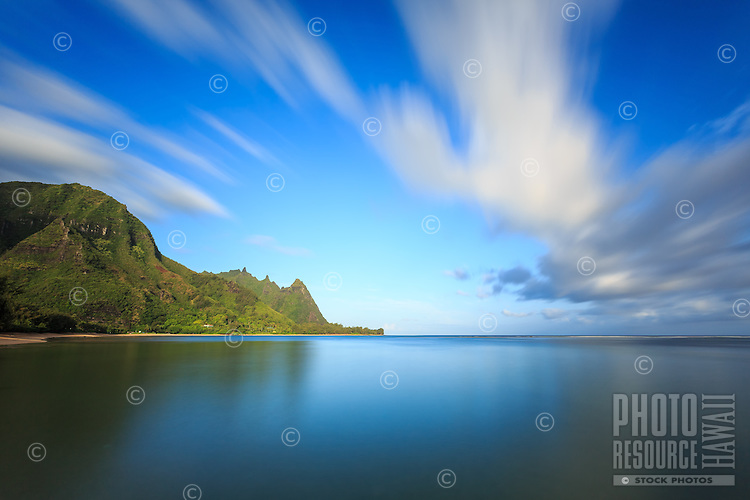 A long exposure of Tunnels Beach at sunrise shows clouds moving over a glassy blue ocean, North Kaua'i.