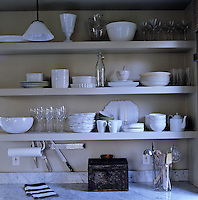 White crockery and glassware is stored on large open shelves in the kitchen