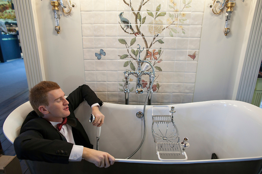 Moscow, Russia, 24/10/2009..A visitor to the Millionaire Fair in Moscow in a bath-tub at a display of luxury English  furnishings.The event has become an annual fixture, attracting thousands of would-be and existing Russian millionaires to view and purchase a wide range of luxury goods. This year however the fair was much smaller, an indication of how the formerly booming Russian economy has been hit by the world financial crisis.