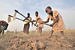 Nyanasek Majak (right) and her sister Joice join their mother, Mary Anyango, and other members of the United Methodist Women in Yei, Southern Sudan, as they prepare a plot of land for planting vegetables. The labor was part of a group food security project. Many of them widows, the women live precariously but at peace after having returned from refugee camps in neighboring Uganda and the Congo in recent years. A 2005 Comprehensive Peace Agreement laid the foundations for peace in Sudan's south after decades of war. NOTE: In July 2011, Southern Sudan became the independent country of South Sudan