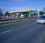 Car blurred speeding past Shell petrol station Britain