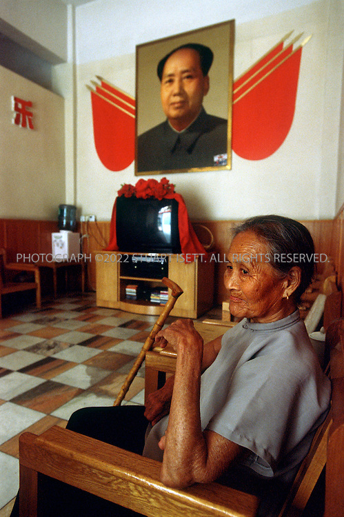 7/15/2005--Nanjie Village, Henan Province, China..Chairman Mao looks over residents in the old age home of Nanjie village, a model communist village in the central province of Henan. the village cares for residents from cradle to grave, even paying for funeral services. The village collectivised its agricultural production and industry in the mid 1980s - when the rest of the country was doing the opposite, introducing market reforms put forward by former leader Deng Xiaoping. ..It continues to be run on Maoist egalitarian lines and has become something of a tourist attraction because of its staunch adherence to the values of the past. ..Photograph By Stuart Isett.All photographs ©2005 Stuart Isett.All rights reserved..Photograph By Stuart Isett.All photographs ©2005 Stuart Isett.All rights reserved.