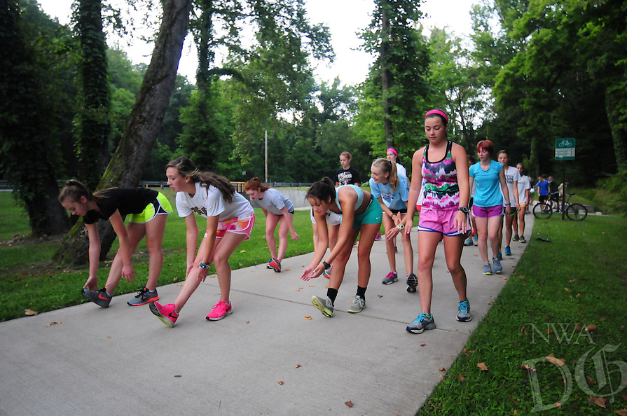 Photo By Spencer Tirey - Bentonville High School Cross County team members practice, in the early morning, , Friday Aug. 15, 2014, on the Greenway Trail in Bentonville.