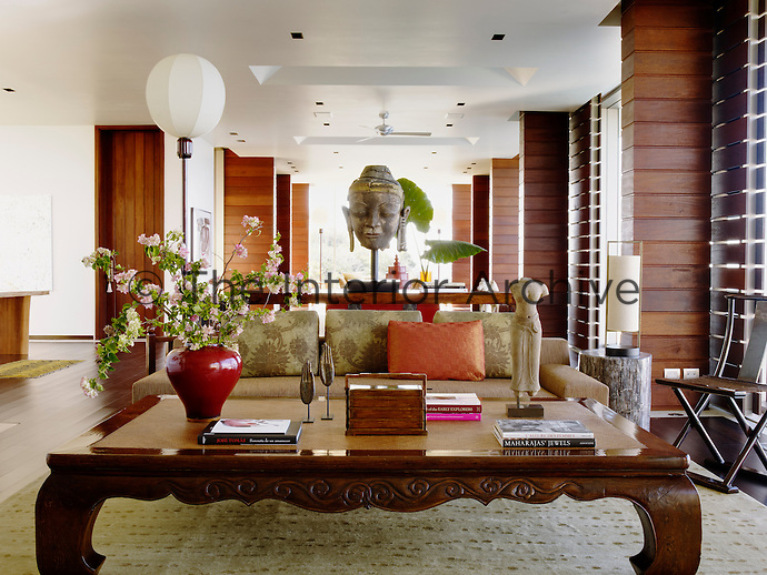 The living room is dominated by a Buddha head and features a sofa by Christian Liaigre and a low Chinese coffee table