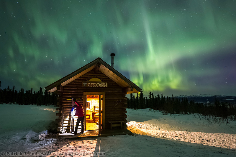 Man prepares cross country skis under the aurora in the White Mountains National Recreation Area
