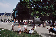 Paris, August 1977. Place des Vosges. August in Paris is a noveable feast. While millions of residents are leaving for their favourite resorts, thousands of foreign tourists are flocking to the French Capital. Nevertheless, genuine Parisians, old and young alike, stay in Paris and mantain the tradition charm.