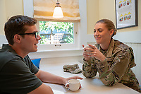 US Military Off Duty woman at home with husband having coffee. Model released, DOD compliant for commercial use.