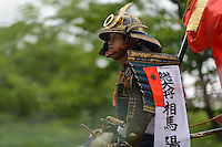 "The samurai ""general"" (seated) leaving Somanakamura shrine, Somanomaoi Festival, Minami-soma City, Fukushima Prefecture, Japan, July 27, 2013. During the four-day-long Somanomaoi Festival members of old samurai families ride horseback through the town in traditional armour.  They also take conduct ceremonies at local shrines, take part in horse races, and compete on horseback to catch a flag launched into the air by fireworks."