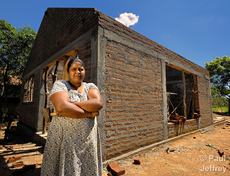 LH Priyanthi stands proudly in front of her home, under construction in Pallemalla on Sri Lanka's tsunami-ravaged southern coast. She lost her home to the waves, and the National Christian Council of Sri Lanka, with support from ACT International, is helping her build a new one.