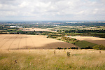 Summer landscape of golden rolling arable fields view north from near Liddington castle, Wiltshire, England towards M4 and Swindon