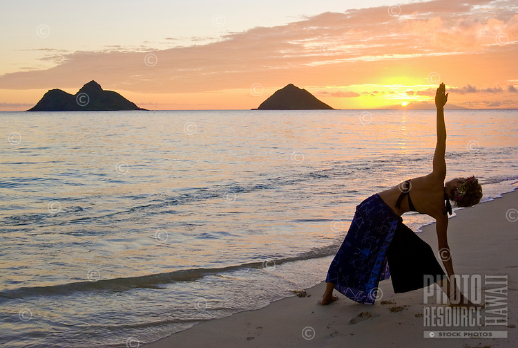 Silhouette of a slim woman in a yoga pose with a beautiful sunrise  in the distance. Photographed at world famous Lanikai beach on the windward side of Oahu, with the Mokulua Islands on the horizon.