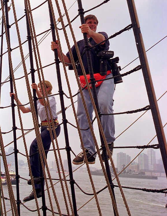a photographer named Andy ?, climbing the rigging of a tall ship in New York harbor on July 5, 2000. Photo by Jim Peppler.