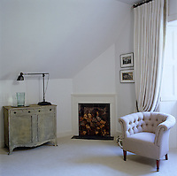 An armchair upholstered in linen stands next to a fireplace in a quiet corner of the bedroom