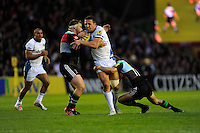 Sam Burgess of Bath Rugby drives through Nick Evans of Harlequins as Matt Shields of Harlequins blocks his path