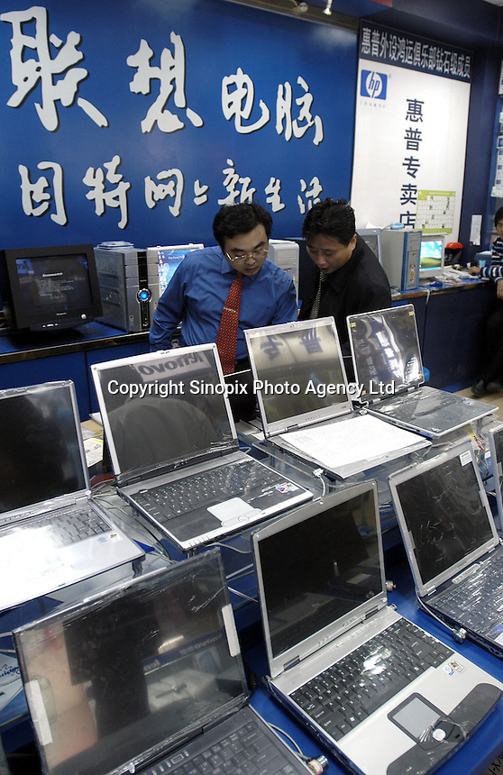 A customer (R) looks at notebook computer in a Lenovo dealership in a Beijing shopping mall, China. Lenovo Group (was formerly known as Legend) is China's largest maker of personal computer. Lenovo announced a definitive agreement under which Lenovo will acquire IBM's Personal Computing Division to form the world's third-largest PC business, bringing IBM's leading enterprise-class PC technologies to the consumer market and giving Lenovo global market reach beyond China and Asia..05-NOV-03