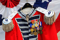 Coat, with service medals, of the Second Company Governor's Foot Guard, New Haven Connecticut, originally adopted from British redcoats in February 1775, scarlet with blue facing, silver braid and buttons.