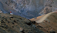 Lone female hiker resting in the crater of HALEAKALA NATIONAL PARK on Maui in Hawaii USA
