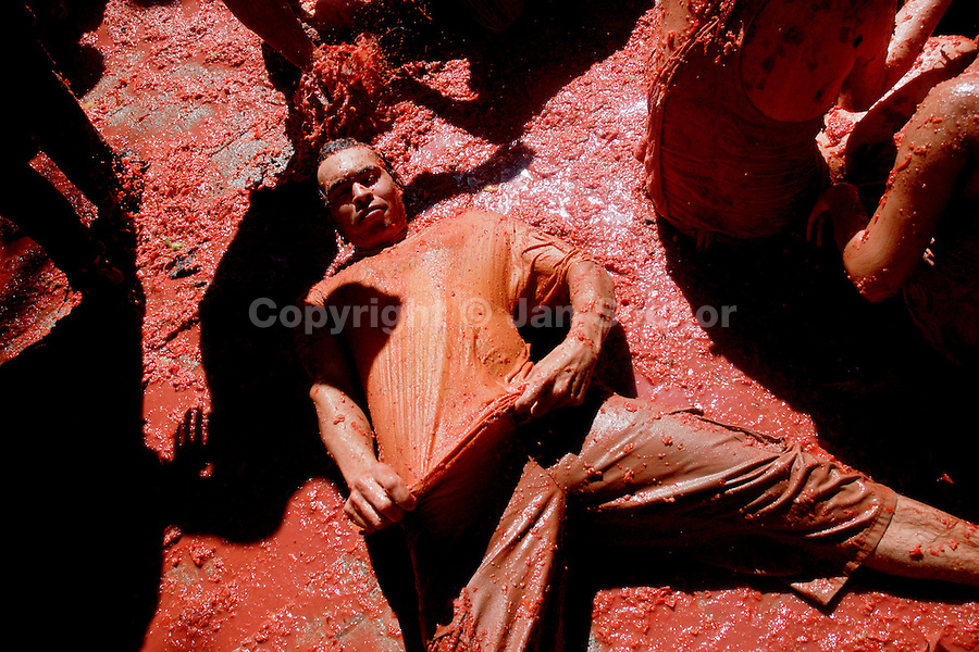 A Spanish boy lies in tomato pulp during La Tomatina festival in Bunol, Spain, 31 August 2006. La Tomatina is a tomato fight held annually in the town of Bunol, close to Valencia. Approximately 40,000 people from all over the world arrive to fight in the battle in which about 50 tons of over-ripe tomatoes are thrown in the street. During the one hour battle everybody fights everybody by throwing squashed tomatoes. The origin of this event is unknown but the Tomatina fights have been recorded since 1945.
