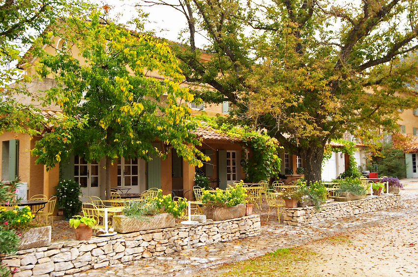 the Domaine de Cabasse hotel and restaurant. Provencal colours, in autumn. The courtyard. with outside seating for the restaurant. Domaine de Cabasse Hotel Restaurant, Alfred and Antoinette Haeni, Séguret, Seguret Cote du Rhone Vaucluse Provence France Europe