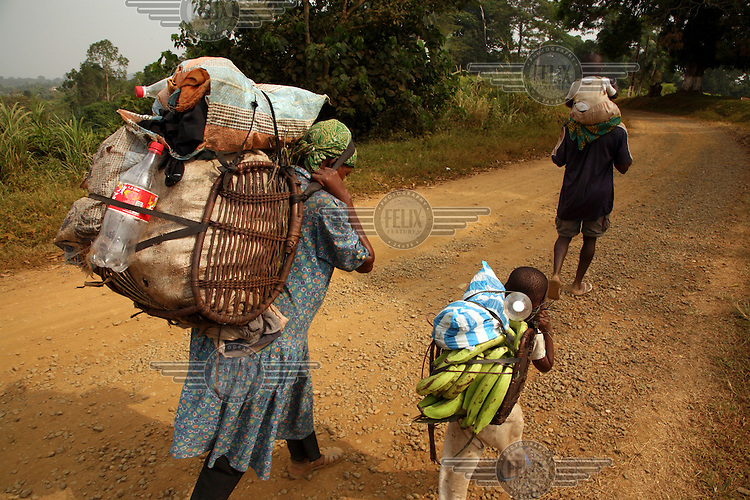 A family walk up a hill as they return from a farm in Kumba.