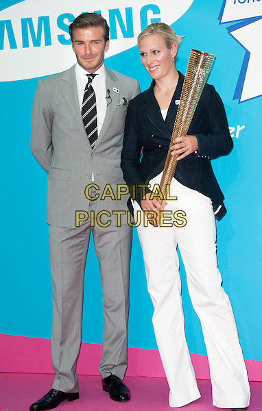 David Beckham & Zara Phillips.Samsung kicks-off its London 2012 campaign 'Everyone's Olympic Games', Canary Wharf, London, England..13th June 2011.full length grey gray suit jacket stubble trousers beard facial hair torch gold blazer black white.CAP/ROS.©Steve Ross/Capital Pictures.