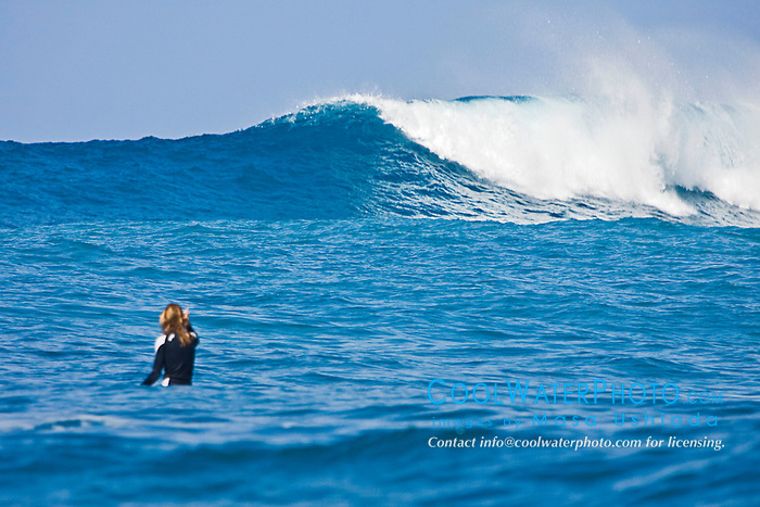 Woman surfer, waiting for a rare big ocean wave in Kona Coast, Keauhou Bay, Big Island, Hawaii, Pacific Ocean.