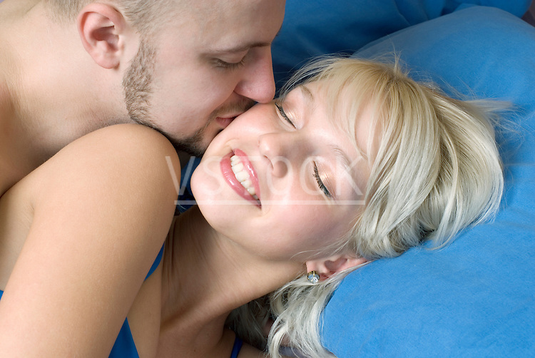 Close-up of young man kissing woman in bed